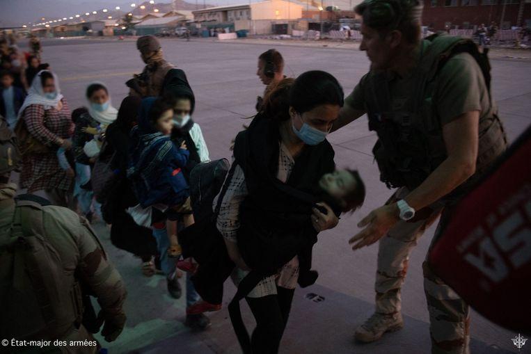 Franse militairen begeleiden evacués die op de luchthaven van Kaboel aan boord gaan van een legervliegtuig. Beeld AFP