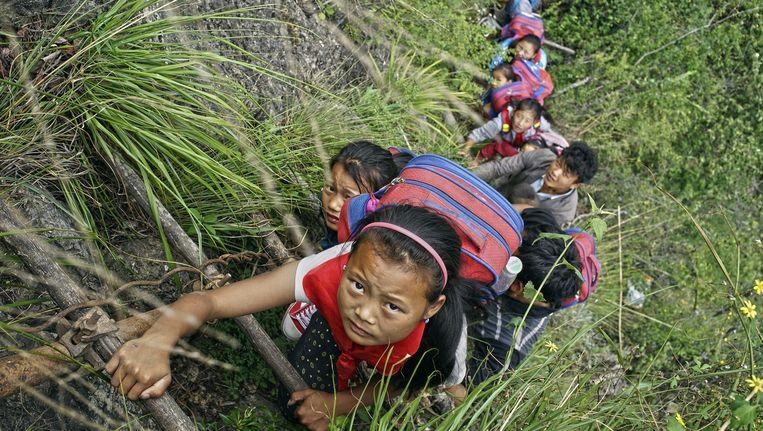Elke twee weken bedwingen de kinderen de 800 meter hoge klif in anderhalf uur. Beeld VCG via Getty Images