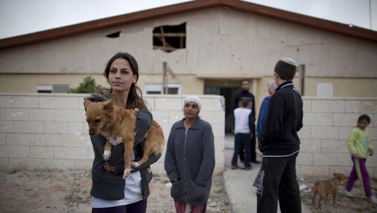 Israëlische burgers bij hun huis dat door Palestijnse raketten werd beschadigd. Beeld AP