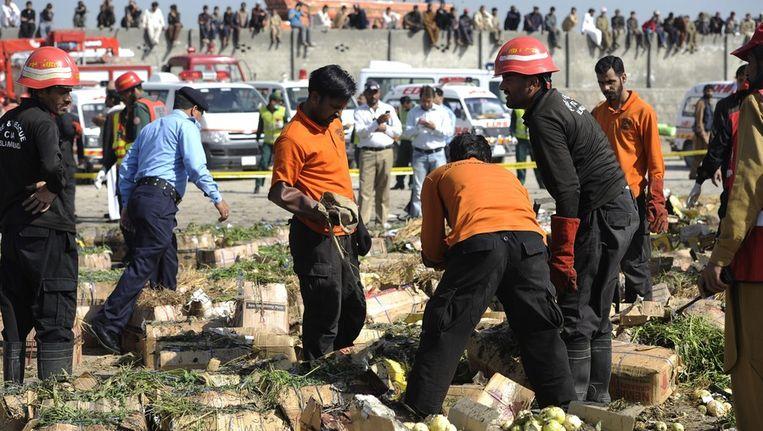 Veiligheidsofficieren en hulpverleners inspecteren de plek waar een bom afging. Beeld epa