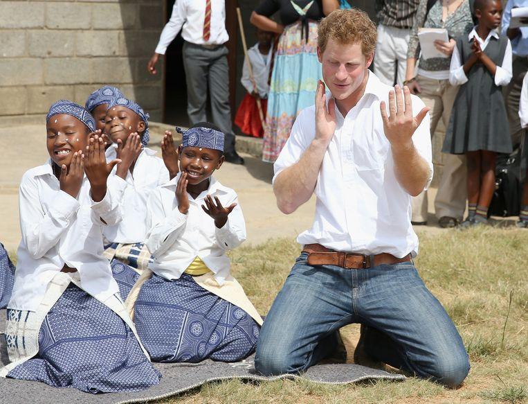 Prins Harry danst met dove kinderen tijdens een bezoek aan Maseru, Lesotho. Beeld getty