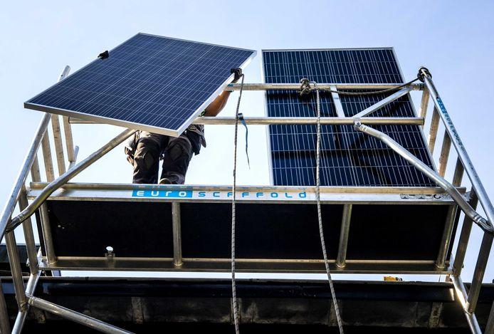 Een installateur plaatst zonnepanelen op het dak van een woonhuis. Zonnepanelen zijn een van de factoren die zorgen voor de groei van de milieusector.