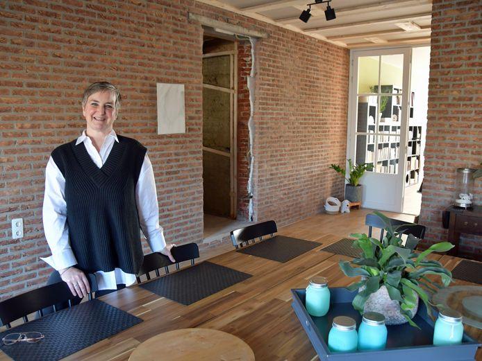 Gezinsouder Marijke van Loon in Terhole bij de grote eettafel in het gezinshuis. In het midden van de foto de toegang naar hun oude woonhuis.