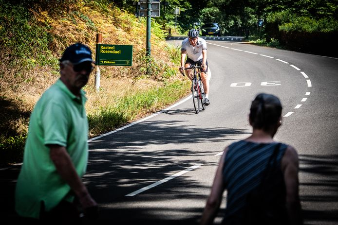 Wielrenners komen in Rozendaal omlaag vanaf de Beekhuizenseweg en rijden de Kerklaan in. Op de voorgrond voetgangers die van Kasteel Rosendael oversteken naar de parkeerplaats.