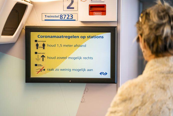 Schermen in de trein tonen informatie over de coronamaatregelen van de NS.