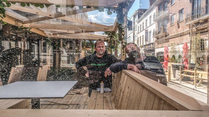 Mathieu Vynckier en Brian Taveirne, achter plexiglas, op het terras van Stradivarius