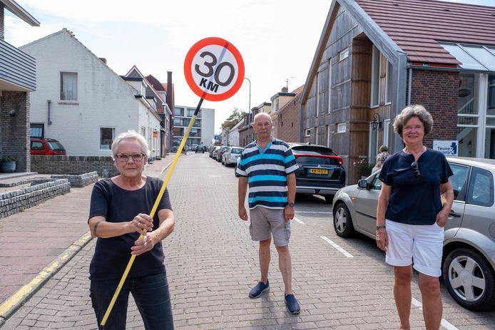 """Jannie Kloeg en Joep en Ria Maas (vlnr)  hebben zelf maar borden gemaakt, in de hoop dat verkeer niet te hard door hun straat rijdt. ,,Want door het slechte onderhoud van de weg geeft dat veel overlast."""""""