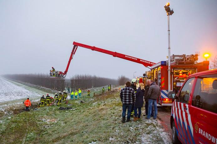 De brandweer rukte met diverse voertuigen uit nadat een auto ondersteboven in een sloot was beland bij Lage Zwaluwe.