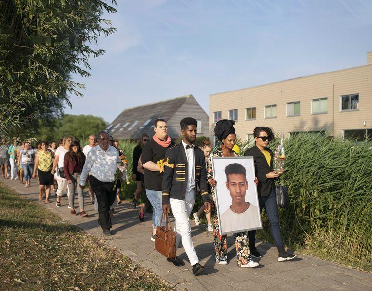 Vrienden en bekenden lopen met een portret van Orlando Boldewijn tijdens een stille tocht ter nagedachtenis aan de 17 jarige jongen die in februari dood werd gevonden.  Beeld ANP