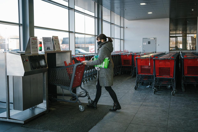 In sommige supermarkten staat ondertussen een 'ontsmettingsmachine' voor winkelkarren. Zoals hier in de Delhaize van Maldegem. Beeld Wouter Van Vooren