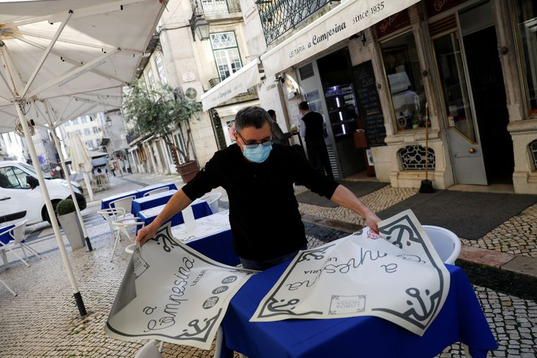 Een horeca-uitbater maakt zijn terras klaar in Lissabon. Beeld Reuters
