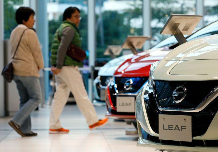 Consumenten lopen in een showroom langs de elektrische auto's Nissan Leaf in Yokohama in Japan. Beeld EPA
