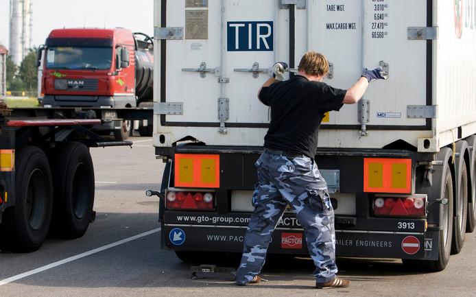Een chauffeur sluit en verzegelt de laadklep van een container achterop zijn wagen.