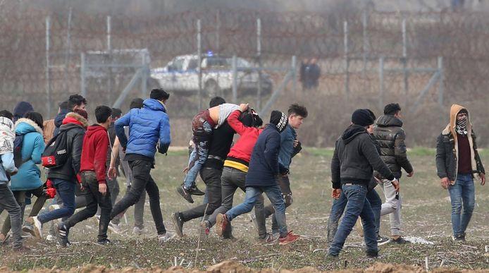 Mensen achter het grenshek probeerden een doorkomen te zoeken.