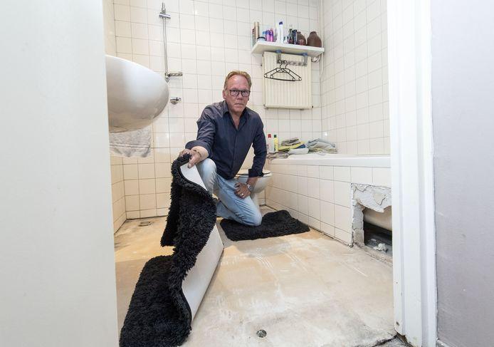"""Johan Pater in de badkamer van de woning aan de Adastraat, waar volgens de bewoners van alles mis is. De badkamer is zo lek als een mandje. """"Opnieuw betegelen en een nieuwe douchebak zijn geen oplossingen."""""""