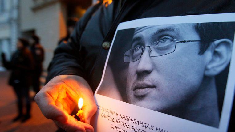 Een vriend van Dolmativ houdt een kaars bij zijn portret tijdens een protest voor de Nederlandse ambassade in Kiev, Oekraïne, waarbij de activist wordt herdacht. Beeld EPA