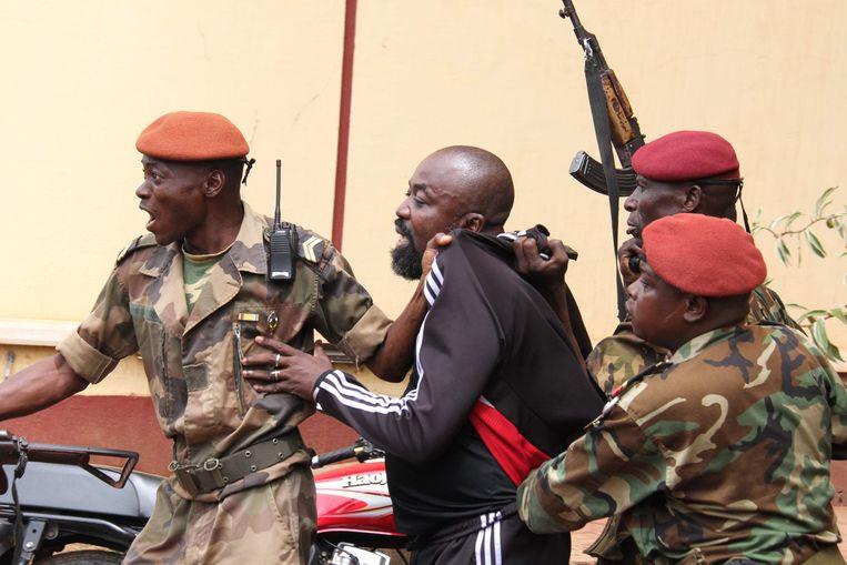 Soldaten van de Centraal-Afrikaanse Republiek (CAR) arresteren de vermeende oorlogsmisdadiger Alfred Yekatom, alias 'Rambo'.   Beeld AFP
