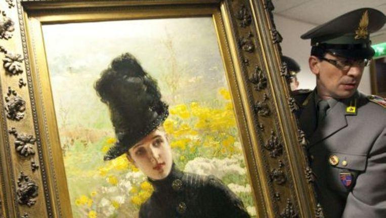 Een agent houdt het schilderij Portret of a Lady van Itailiaanse Giuseppe De Nittis vast. Foto ANP Beeld