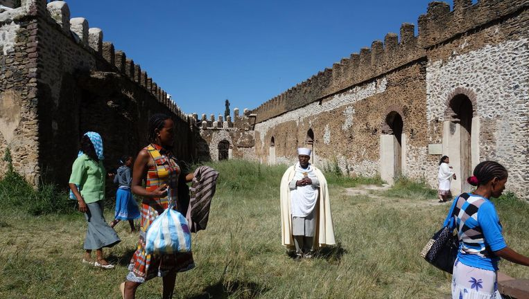 Een orthodox-christelijke priester en andere bezoekers in een keizerlijk kasteel in Gondar. Binnen een ommuring bevinden zich meerdere ruïnes. Bij de stad is ook een keizerlijk badhuis. Beeld Wim Bossema