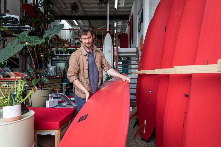 Eigenaar Simon James in zijn nieuwe surfclub: 'Een bibliotheek aan boarddesign.' Beeld Dingena Mol