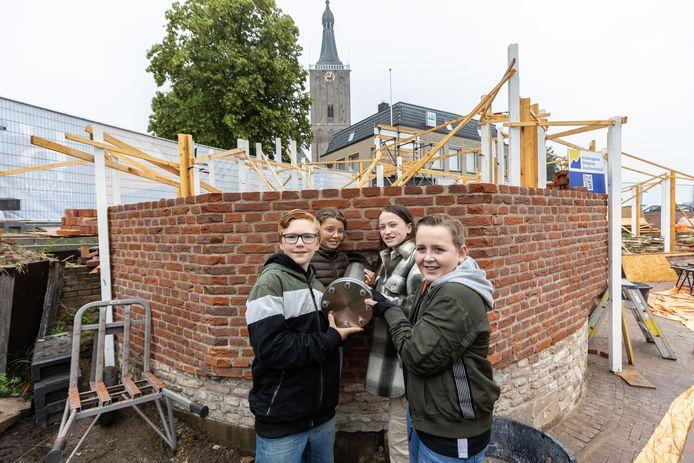 Robin Holthuis, Tony de Wit, Fenna Fransen en Justin Noordman, leerlingen uit groep 8 van De Toermalijn en Het Anker,  plaatsen een tijdcapsule in de Veerpoort in Hasselt. Het is de bedoeling dat die capsule over honderd jaar wordt geopend.