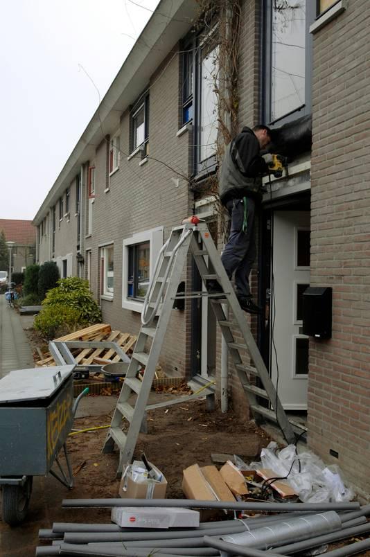 Bouwvakker van Sylva Bouw aan het werk in De Helmerhoek in Enschede.