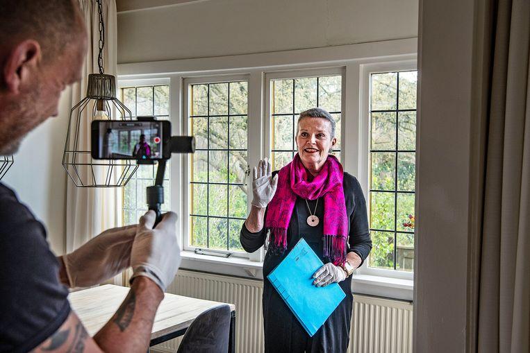 Makelaar Jeanine van der Sanden maakt een video om potentiële kopers een eerste indruk te geven van een woonhuis in Haarlem. Beeld Guus Dubbelman / de Volkskrant