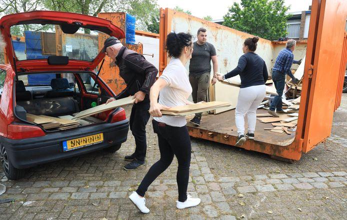 Tiffany Christiaens (tweede van rechts, in de container) lost met familieleden een vracht in een van de gemeentelijke containers op het Minister Lelyplein in Sluiskil.