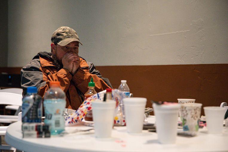 Een man blaast zijn handen warm in een opvangcentrum in Odessa, Texas. Beeld AP