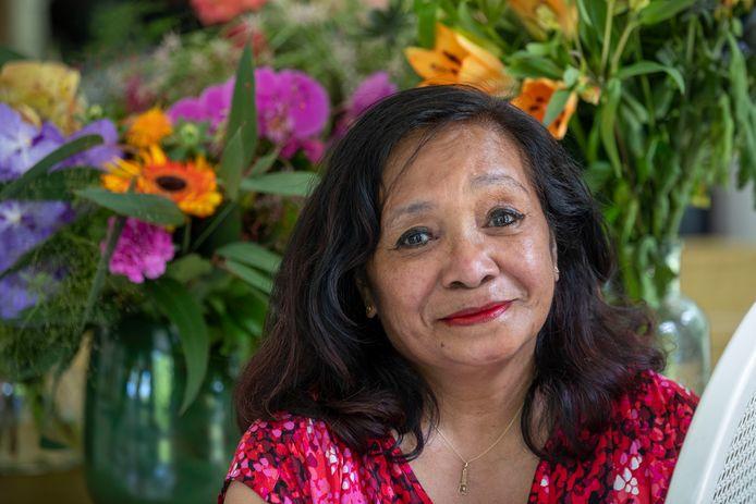 Els Hoetmer-Sapuletej neemt afscheid van het onderwijs, op achtergrond de bloemen die zij heeft gekregen van oud-leerlingen.