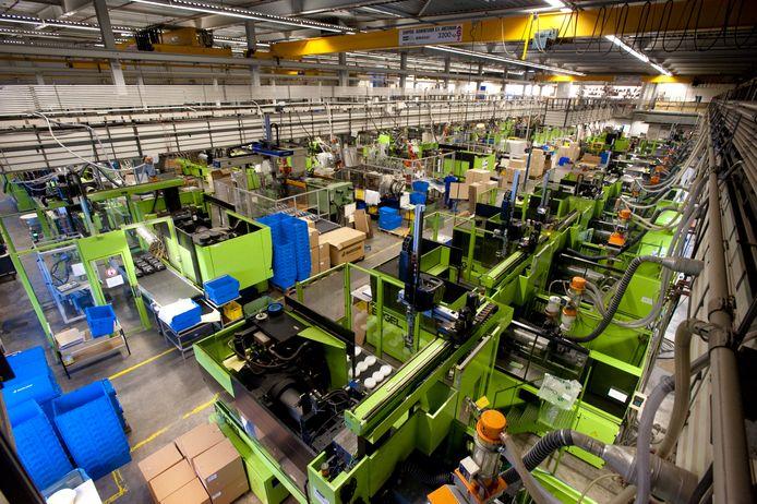 Een productiehal met spuitgietmachines van DPI in Geldrop.  Kunststof wordt onder hoge druk ingespoten in een matrijs met de vorm van het gewenste product. Een robot haalt de producten uit de matrijs en plaatst ze op de  band.