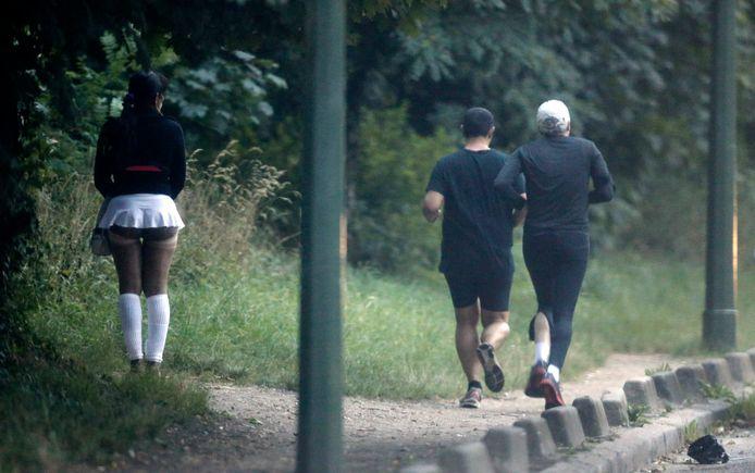 Joggers lopen voorbij een tippelende prositituee aan het Bois de Boulogne, foto uit 2013.