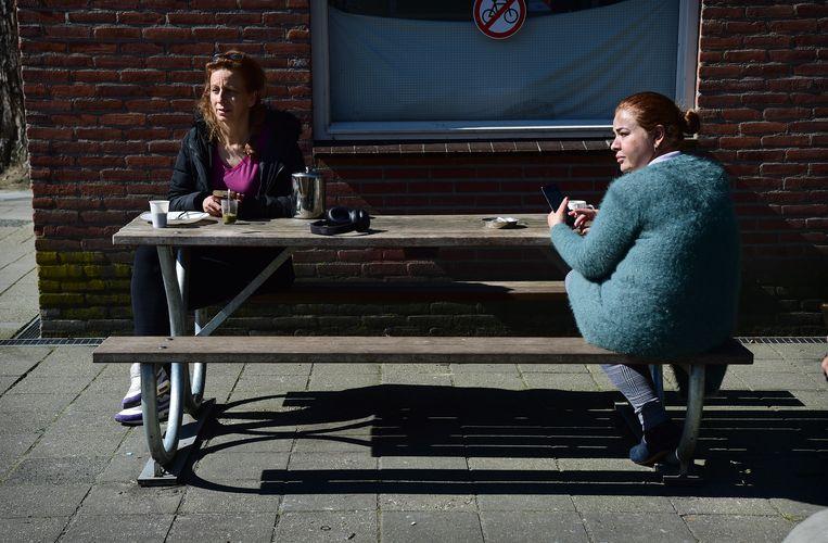 Asielzoekers van het azc in Wageningen scheppen een luchtje met het mooie weer, maart 2020.  Beeld Marcel van den Bergh