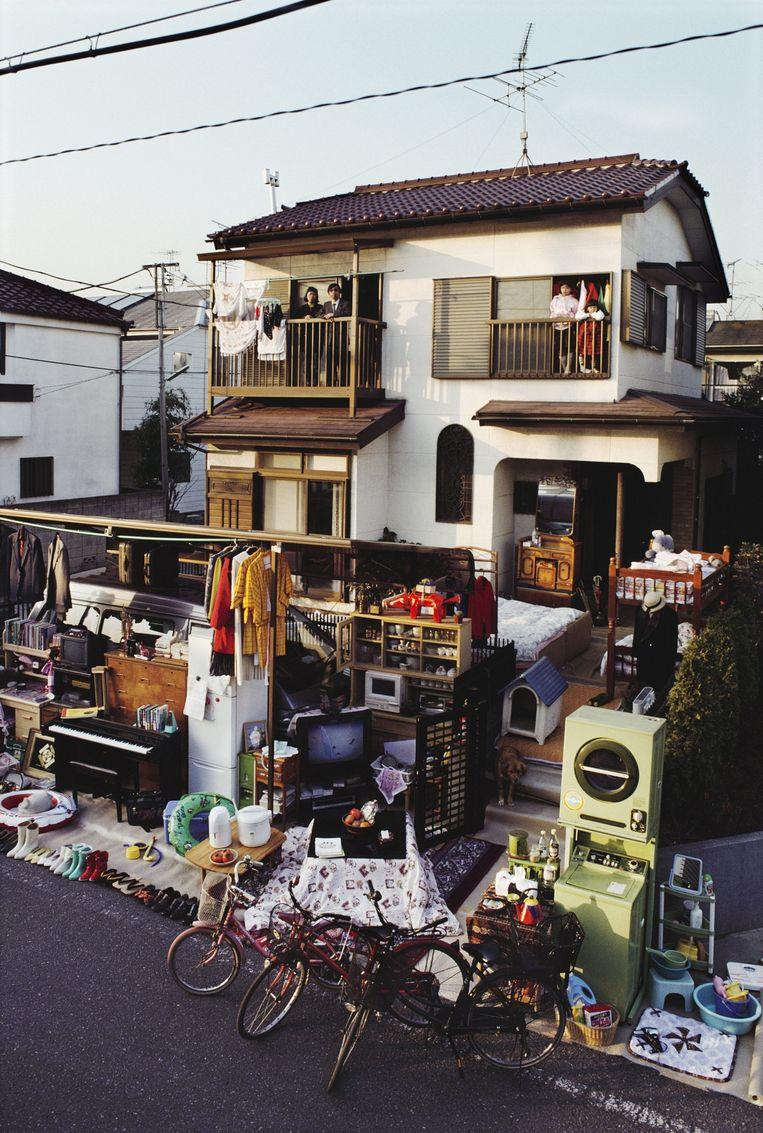 Een Japans gezin met twee kinderen heeft al hun spullen uitgestald voor het huis. Beeld Peter Menzel