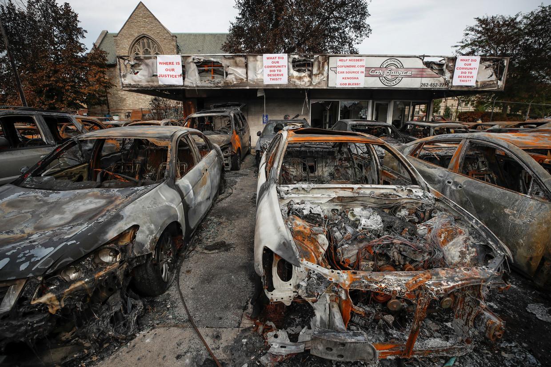 Uitgebrande auto's in de Amerikaanse stad Kenosha op maandag. In de stad zijn al een week gewelddadige protesten aan de gang tegen politiegeweld. Trump bezoekt Kenosha dinsdag. Beeld Reuters