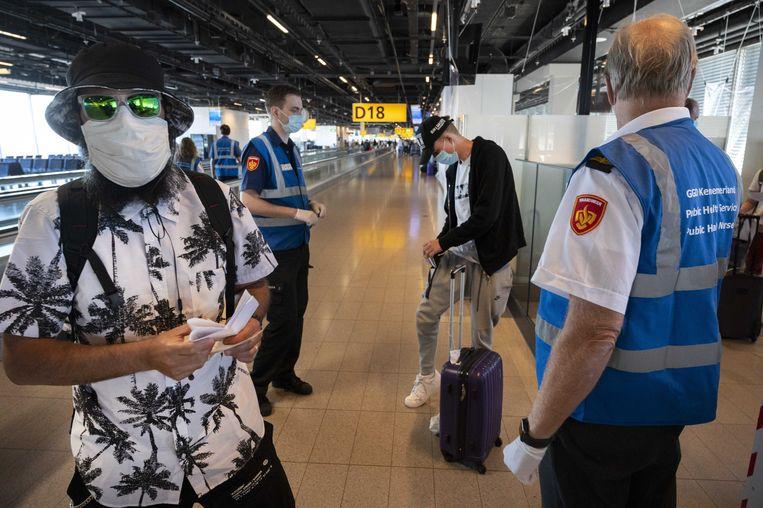Medewerkers van de GGD ondervragen vakantiegangers op Schiphol.  Beeld ANP