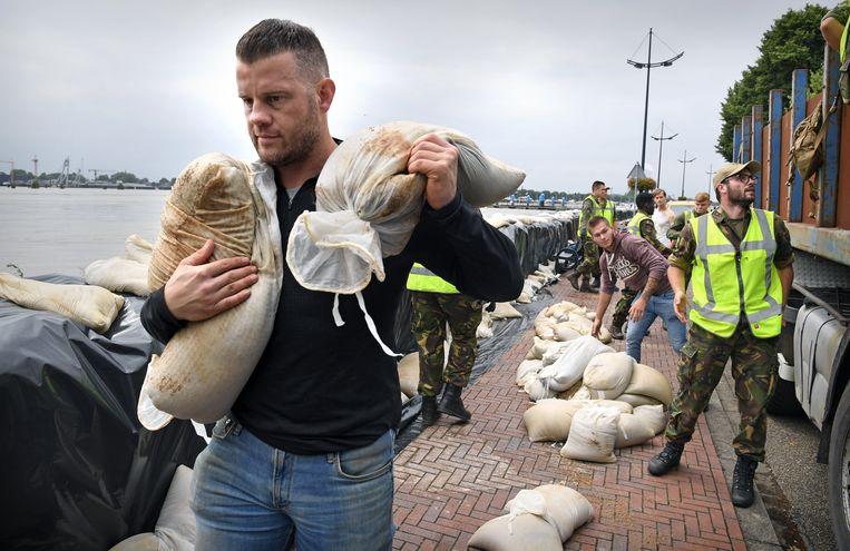 Militairen leggen in Wessem een nooddijk aan met zandzakken. Enkele inwoners van het dorp helpen mee.  Beeld Marcel van den Bergh