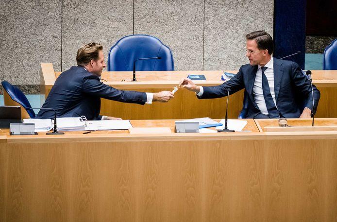 Minister Hugo de Jonge (l) en premier Mark Rutte (r).