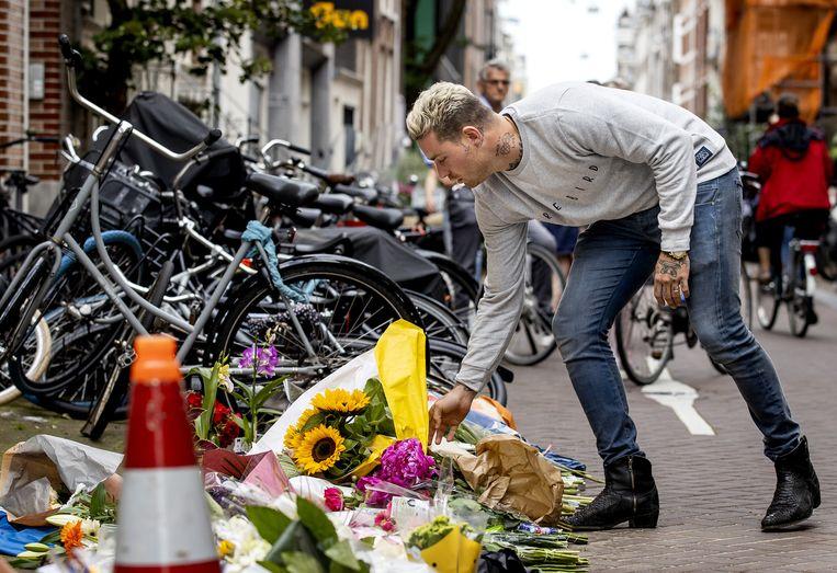 Douwe Bob laat een bos bloemen aan Peter R. de Vries achter in de Lange Leidsedwarsstraat in het centrum van Amsterdam. De misdaadverslaggever ligt zwaargewond in het ziekenhuis, na een aanslag op zijn leven. Beeld ANP