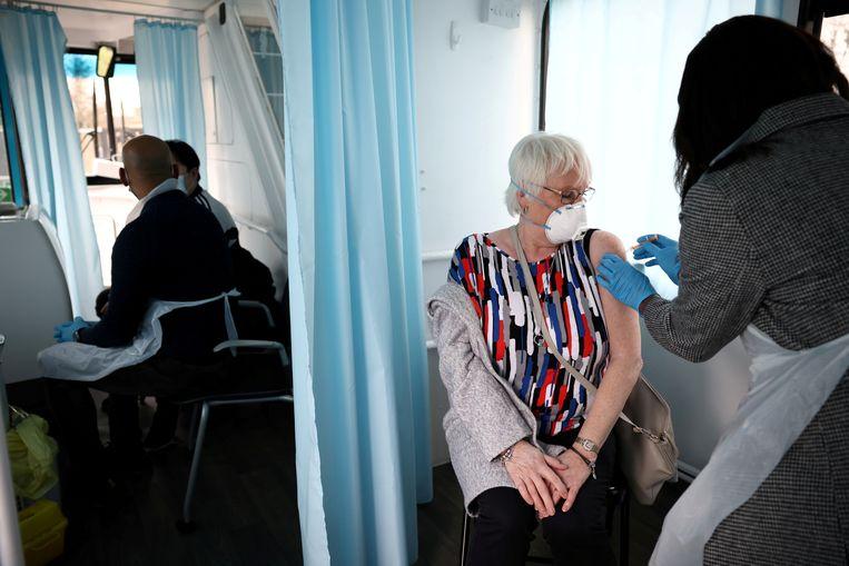 Een Britse vrouw wordt in Londen gevaccineerd tegen corona. Er zijn op dit moment al 21 miljoen prikken uitgedeeld in het Verenigd Koninkrijk.  Beeld REUTERS