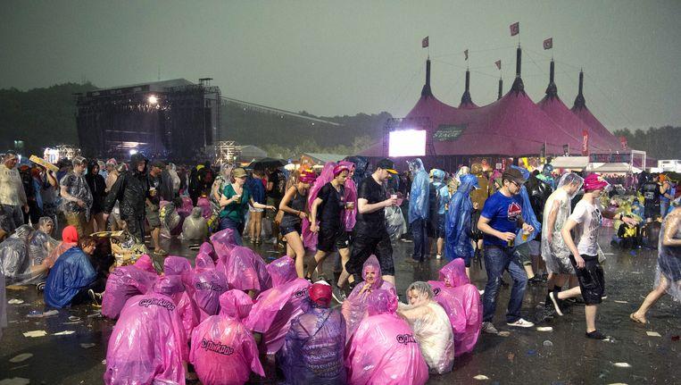 Bezoekers van Pinkpop 2014 schuilen voor het noodweer. Beeld ANP