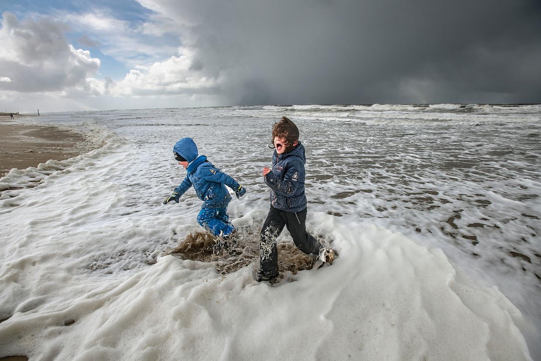 Twee broertjes spelen in de onstuimige zee. Beeld Guus Dubbelman / de Volkskrant