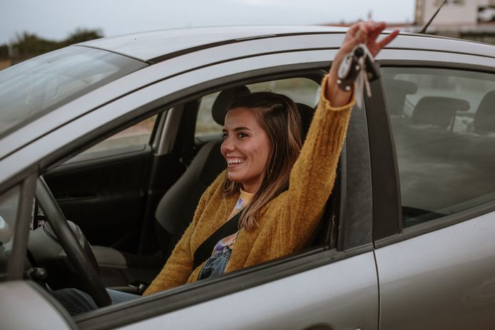 A young woman with a happy expression on her face, holding her new car keys