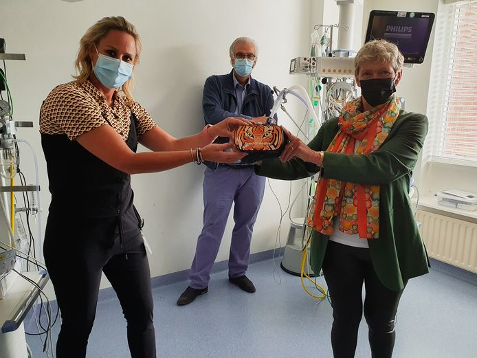 Penningmeester van de stichting, Arna de Wit, overhandigt één van de brillen aan afdelingshoofd Marieke van Splunter.