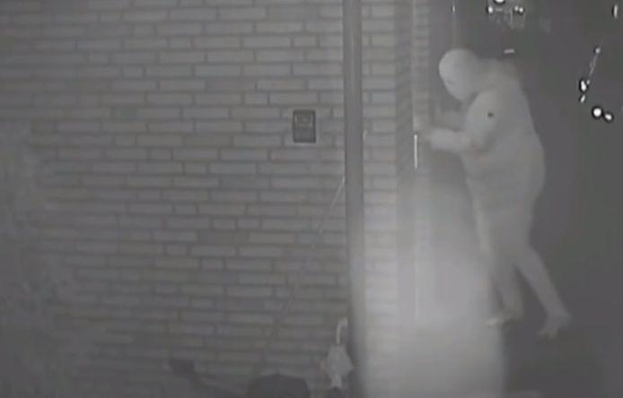 Een screenshot uit de uitzending van Opsporing Verzocht waarin aandacht werd besteed aan de overval op de woning in Zaltbommel. Een gemaskerde overvaller probeert het huis aan de Thorbeckestraat binnen te komen.
