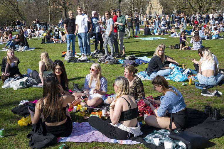Bezoekers in het Vondelpark  in Amsterdam eind maart op een mooi zonnige dag. De toegang tot het park werd tijdelijk afgesloten omdat het te druk is. Beeld ANP, Evert Elzinga