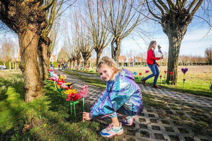 Een meisje plant een papieren bloem op de oprijlaan.