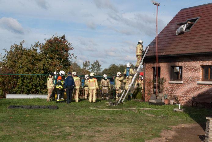 Brandweermannen kijken of er onder de dakpannen nog moet geblust worden.