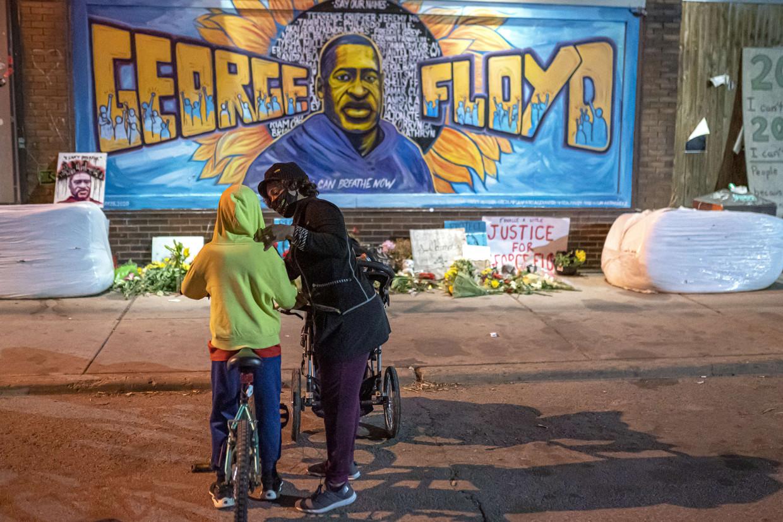 Een vrouw praat met haar zoon voor een muurschildering van George Floyd in Minneapolis. Beeld AFP