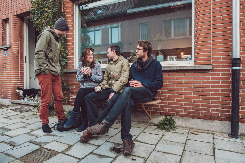 """Jesse, Wiske, Anton en Simon op een gevelbank in de Drapierstraat in Mariakerke (Gent). """"We creëren opnieuw een klein, gezellig plekje"""", zegt Anton Christiaens, een van de bezielers van het bedrijfje Gevelbank. Beeld Wouter Van Vooren"""